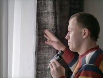 O homem novo olha para fora a janela com binóculos, close-up imagens de stock royalty free