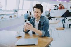 O homem novo ou o freelancer atrativo com móbil estão sentando-se no café e no café bebendo imagens de stock royalty free