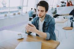 O homem novo ou o freelancer atrativo com móbil estão sentando-se no café e no café bebendo foto de stock