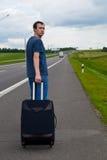 O homem novo pendente na estrada com mala de viagem Imagem de Stock