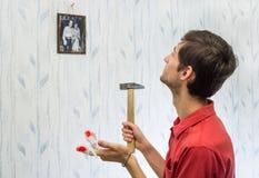 O homem novo pendurou imagens na parede, melhorando o interior Foto de Stock