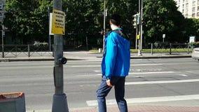 O homem novo pressiona o botão, esperando até a luz verde e começa a cruzar a estrada Um homem com uma inabilidade, limping video estoque