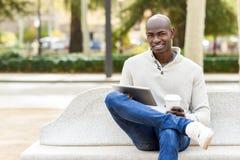 O homem novo preto com tablet pc e leva embora o café fotografia de stock royalty free