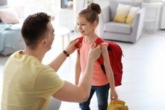 O homem novo que ajuda sua criança pequena prepara-se para a escola imagens de stock