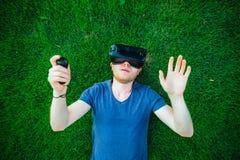 O homem novo que apreciam auriculares dos vidros da realidade virtual ou os espetáculos 3d que encontram-se no gramado verde na c imagens de stock