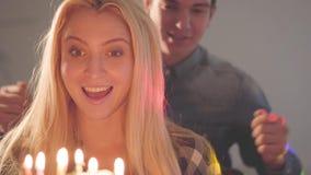 O homem novo que cobre os olhos da senhora consideravelmente loura, a seguir deixou-a ver o bolo com muitas velas A mulher tem o  vídeos de arquivo