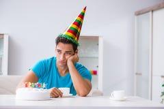 O homem novo que comemora o aniversário apenas em casa imagem de stock royalty free