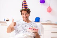 O homem novo que comemora seu aniversário no hospital foto de stock royalty free