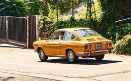 O homem novo que conduz o cupê amarelo do esporte de Fiat 850 do vintage liberou-se cerca de 1970 em Itália Fotografia de Stock Royalty Free