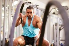 O homem novo que dá certo com batalha ropes em um gym Foto de Stock Royalty Free