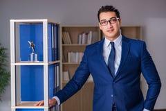 O homem novo que está ao lado da prateleira com dobradores Fotografia de Stock