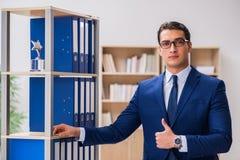 O homem novo que está ao lado da prateleira com dobradores Imagens de Stock