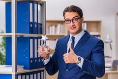 O homem novo que está ao lado da prateleira com dobradores Imagem de Stock