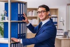 O homem novo que está ao lado da prateleira com dobradores Foto de Stock Royalty Free