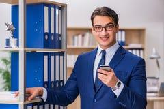 O homem novo que está ao lado da prateleira com dobradores Imagens de Stock Royalty Free