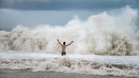 O homem novo que está contra o mar acena com respingo em um tempo nebuloso da tempestade Fotografia de Stock Royalty Free