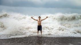 O homem novo que está contra o mar acena com respingo em um tempo nebuloso da tempestade Fotos de Stock Royalty Free