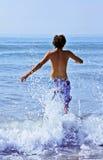 O homem novo que funciona no mar Fotografia de Stock Royalty Free