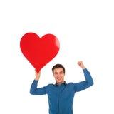 O homem novo que guarda o coração vermelho grande está comemorando o amor Foto de Stock