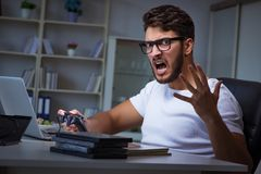 O homem novo que joga o muito tempo dos jogos tarde no escritório fotografia de stock