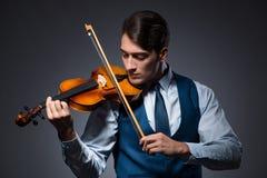 O homem novo que joga o violino na sala escura imagem de stock