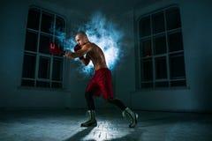 O homem novo que kickboxing no fumo azul imagem de stock