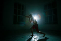 O homem novo que kickboxing no fundo preto fotografia de stock royalty free