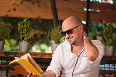 O homem novo que lê um livro tem um riso Imagem de Stock Royalty Free