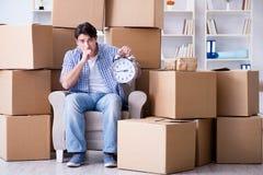 O homem novo que move-se dentro para a casa nova com caixas Imagem de Stock