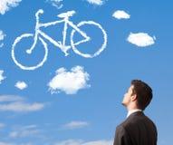 O homem novo que olha a bicicleta nubla-se no céu azul Foto de Stock Royalty Free