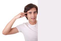 O homem novo que prende um quadro de avisos em branco, gesticulando tem Fotografia de Stock