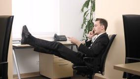 O homem novo que senta-se no escritório, falando no telefone celular e e ajusta o condicionador de ar 60 fps video estoque