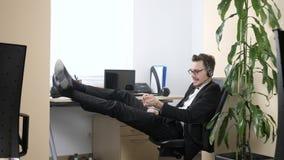 O homem novo que sentam-se no escritório, falando em auriculares e os apertos entregam o expansor 60 fps video estoque