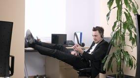 O homem novo que sentam-se no escritório, falando em auriculares e os apertos entregam a expansor 60 fps vídeos de arquivo