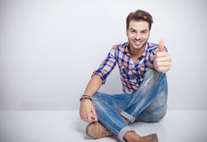 O homem novo que sorri ao mostrar os polegares levanta o gesto Fotos de Stock Royalty Free