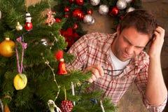 O homem novo que tenta reparar a árvore de Natal ilumina-se imagem de stock
