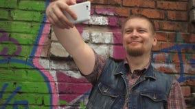 O homem novo que toma o selfie com telefone celular e aproxima-se de uma parede pintada com grafittis video estoque