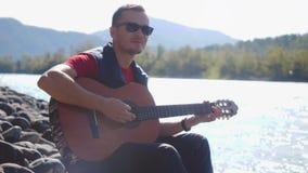 O homem novo que veste óculos de sol joga em uma guitarra que senta-se pelo rio da montanha no dia ensolarado no movimento lento  filme