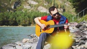 O homem novo que veste óculos de sol que os jogos em uma guitarra cantam a música senta-se pelo rio da montanha no dia ensolarado video estoque