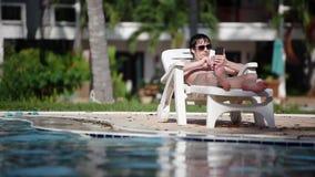 O homem novo que veste óculos de sol usa o telefone celular ao encontrar-se sunbed sobre nadando o fundo da associação da infinid filme