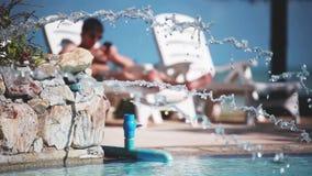 O homem novo que veste óculos de sol usa o telefone celular ao encontrar-se sunbed sobre pela piscina com água de pulverização no video estoque