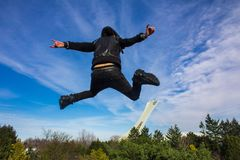 O homem novo que veste um casaco de cabedal e umas calças magros é saltar alto foto de stock royalty free