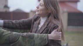 O homem novo que veste o uniforme militar veio em casa e feliz abra?ando sua esposa alegre bonita no fundo da rua video estoque