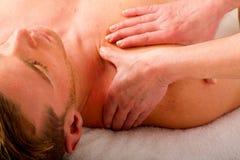 O homem novo recebe a massagem aos ombros fotos de stock royalty free