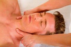O homem novo recebe uma massagem da garganta fotografia de stock