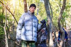 O homem novo recolhe o lixo na floresta fotos de stock royalty free