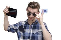 O homem novo registrou o bilhete para o curso através da tabuleta Fotografia de Stock Royalty Free