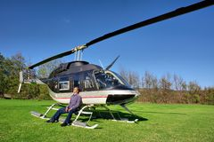 O homem novo relaxa ao lado do helicóptero pequeno foto de stock royalty free