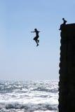O homem novo salta na água. foto de stock