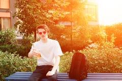 O homem novo senta e dá uma garrafa da cidra no parque sunlight Imagens de Stock Royalty Free